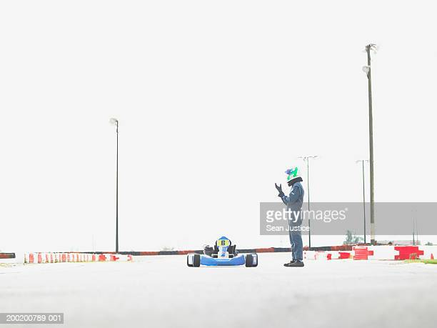 Go-cart racer on track putting on glove, side view