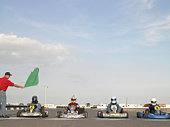 Go-cart racers at start line, man waving green flag