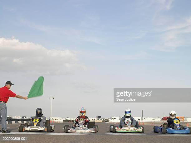 Go-cart racers at start line, man waving green flag