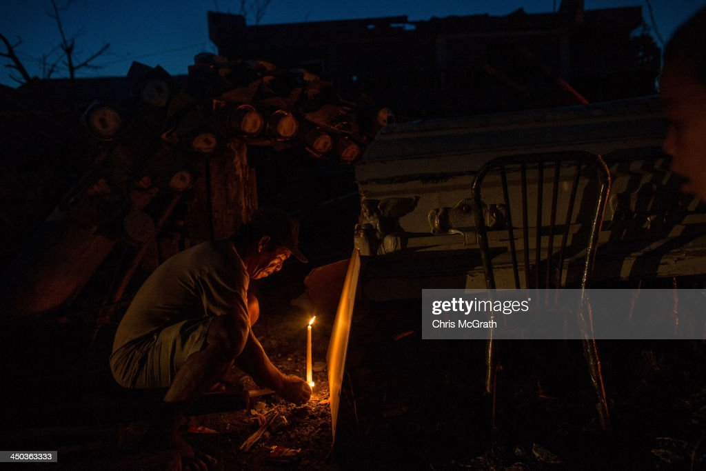 Godofredo Awaaw lights candles on the roadside next to the coffin of his daughter inlaw in Tacloban City on November 18 2013 in Leyte Philippines...