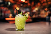 Front view of a Godzilla cocktail on a bar counter. The background of the image is defocused lights and the back of the bar. This cocktail has Kiwi as a garnish on the cold drink.