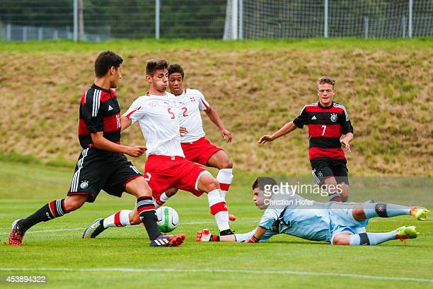 Goerkem Saglan and Patrick Sontheimer of Germany compete for the ball with Jan Bamert Kevin Rueegg and Goalkeeper Joao Paulo Castanheira of...