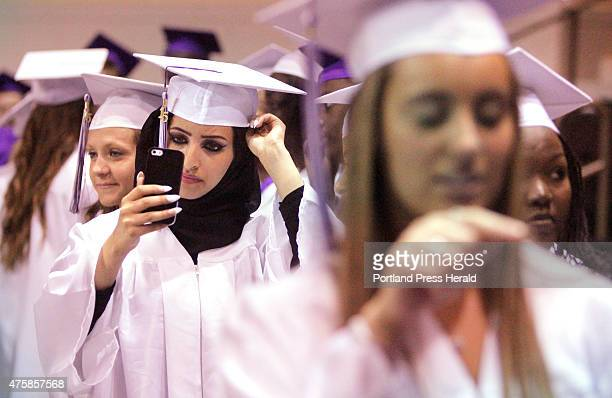 Gofran Ali uses her phone to help adjust her cap while waiting in line to start the processional at Deering High School's graduation at the Cross...