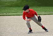 7 year old boy going toward a baseball in the field, summer Naperville, Illinois  USA