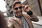 Self portrait of handsome young man in casual wear smiling and adjusting his eyewear while standing outdoors