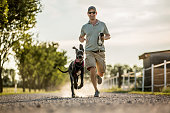 A guy is running next to his boar hound during the sunset.