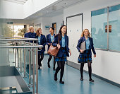 Group of students are walking down the school corridor together wearing uniform.