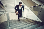 Blurred motion of businessman going upstairs in office building