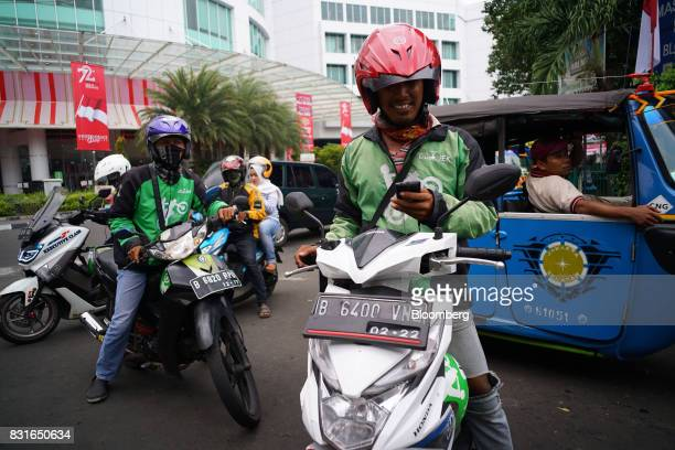GoJek motorcycle drivers foreground and left stand with their motorbikes as a driver for Uber Technologies Inc's UberMotor service rear and a bajaj...