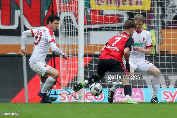 Gojko Kacar of Augsburg Martin Hinteregger of Augsburg and Florian Niederlechner of Freiburg battle for the ball during the Bundesliga match between...