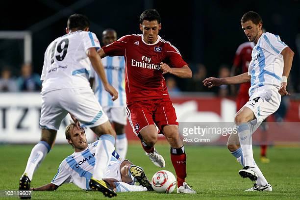 Gojko Kacar of Hamburg is challenged by Mate Ghvinianidze Daniel Bierofka and Florin Lovin of Muenchen during a preseason friendly match between 1860...