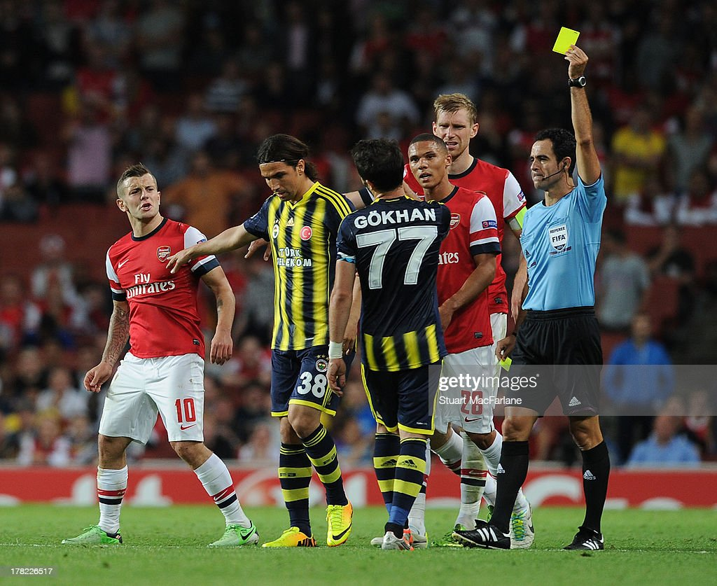 Gokhan Gonul of Fenerbahce is booked by referee Carlos Velasco Carballo for a foul on (L) Arsenal's <a gi-track='captionPersonalityLinkClicked' href=/galleries/search?phrase=Jack+Wilshere&family=editorial&specificpeople=5446655 ng-click='$event.stopPropagation()'>Jack Wilshere</a> during the UEFA Champions League Play Off Second leg match between Arsenal FC and Fenerbahce SK at Emirates Stadium on August 27, 2013 in London, England.