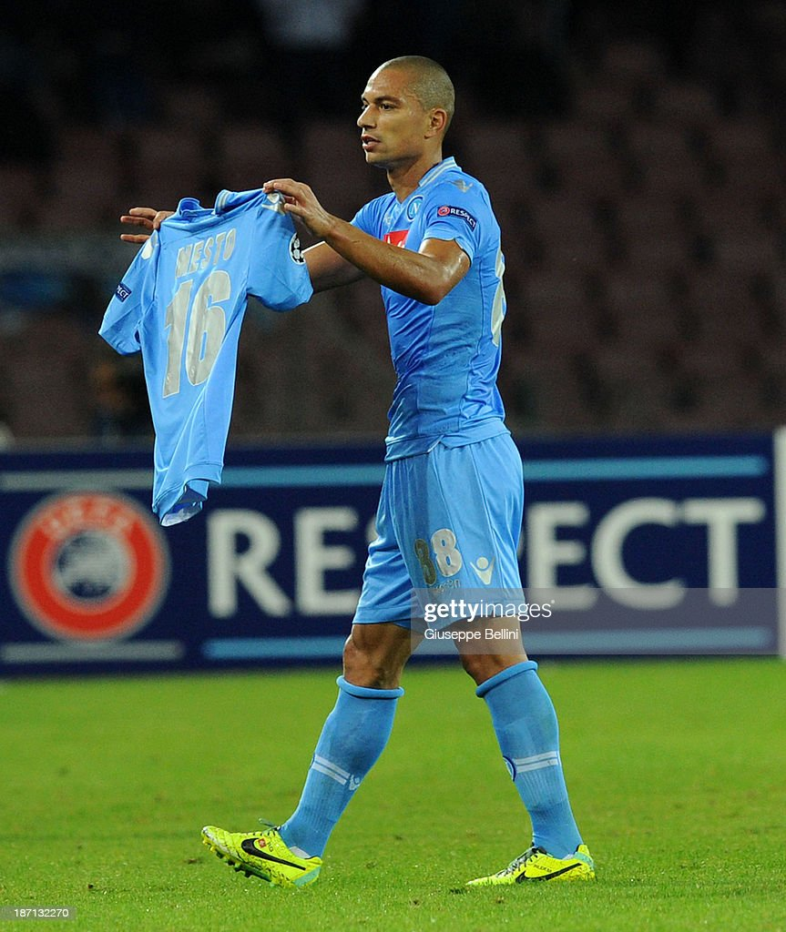 Gokhan Inler of Napoli celebrates with the shirt of his injured team-mate Giandomenico Mesto after scoring their first goal during the UEFA Champions League Group F match between SSC Napoli and Olympique de Marseille at Stadio San Paolo on November 6, 2013 in Naples, Italy.