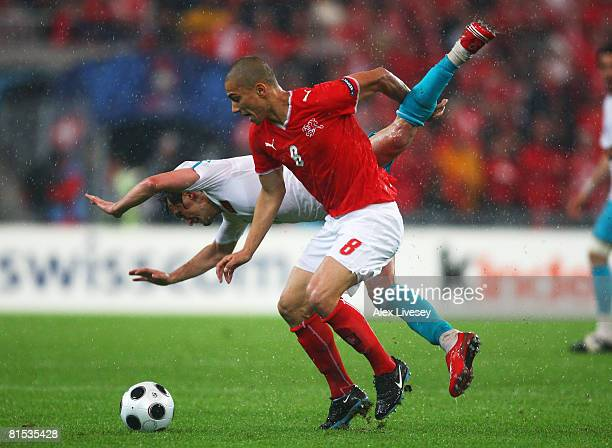 Gokhan Inler of Switzerland tackles Tuncay Sanli of Turkey during the UEFA EURO 2008 Group A match between Switzerland and Turkey at St JakobPark on...