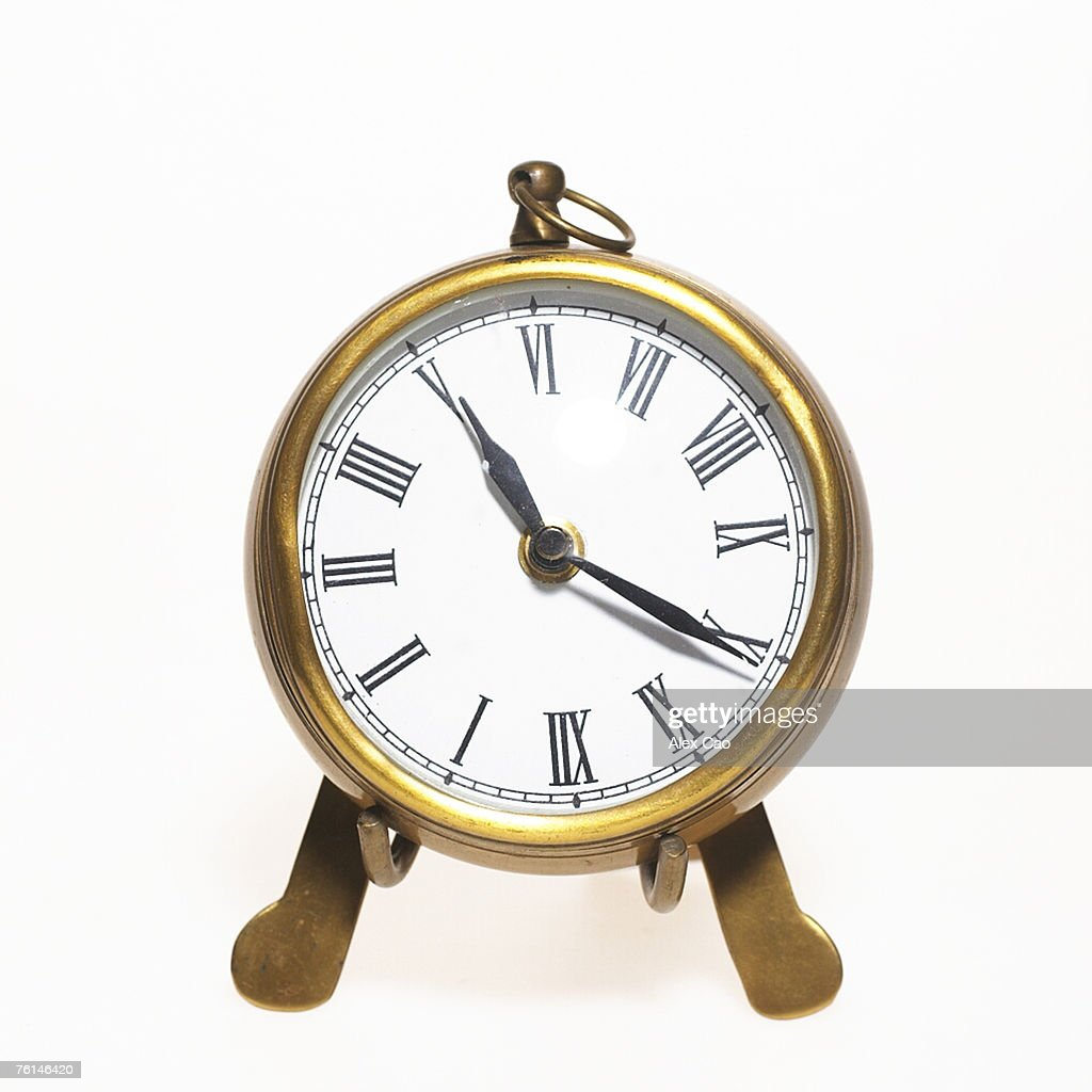 Gold analogue table clock with roman numerals against white background