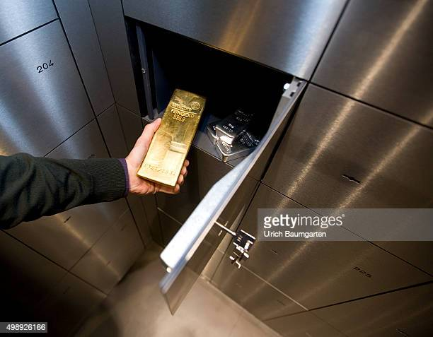 Gold and silver bullions in the strong room of pro aurum Goldhouse in Munich Hand puts a 125 kg gold bullion in a deposit box