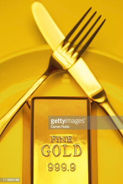 A gold bar on a plate with a knife and fork