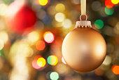 Gold Bauble Hanging On Decorated Tree