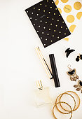 Black and gold on white. Woman's makeup and accessories, polka dot note pad. Beauty blog flat lay. Negative space