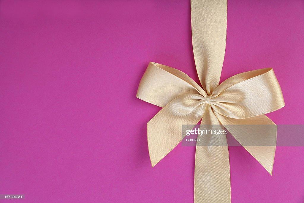 Lazo de oro sobre fondo rosa : Foto de stock