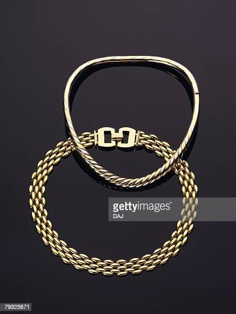 Gold bracelets, high angle view, black background