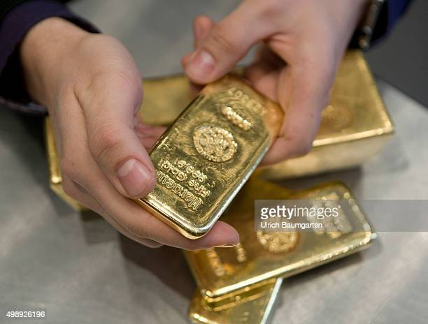 Gold bullions in the strong room of the pro aurum goldhouse in Munich Hands with 1 kg and 125 kg gold bullions