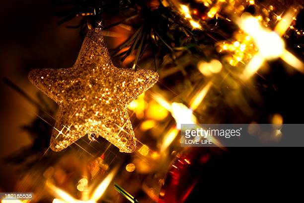 Gold Christmas star decoration on a tree