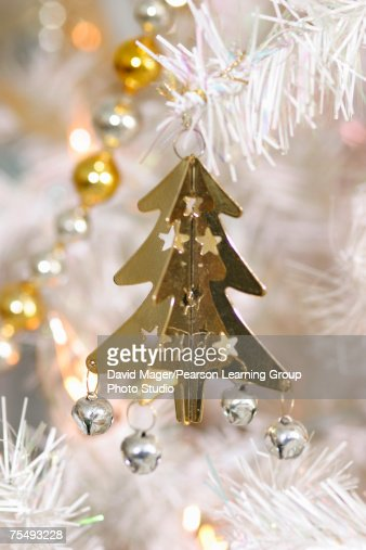 Gold Christmas tree decoration with small bells and stars attached, suspended from silver branch : Stock Photo