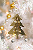 Gold Christmas tree decoration with small bells and stars attached, suspended from silver branch
