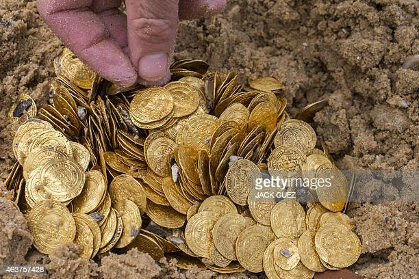 Gold coins which were recently found on the seabed off Israel's Mediterranean coast are seen displayed in sand in the Israeli town of Caesarea on...