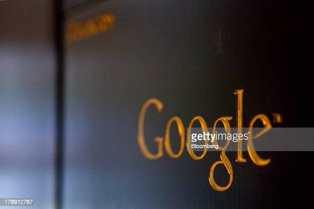 A gold colored Google Inc logo sits on a sign outside the company's offices in Berlin Germany on Friday Aug 16 2013 Google based in Mountain View...