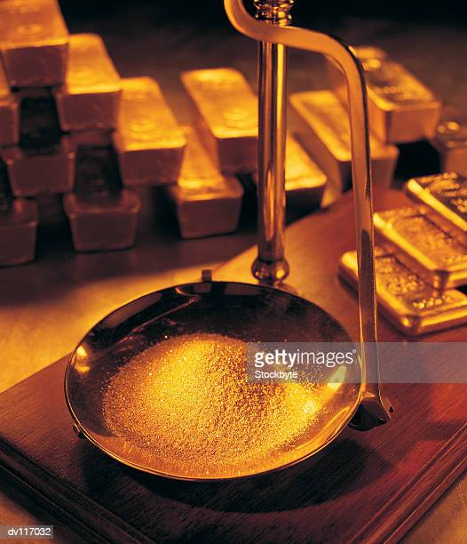 Gold dust being weighed on scales, with stacks of gold bars in background