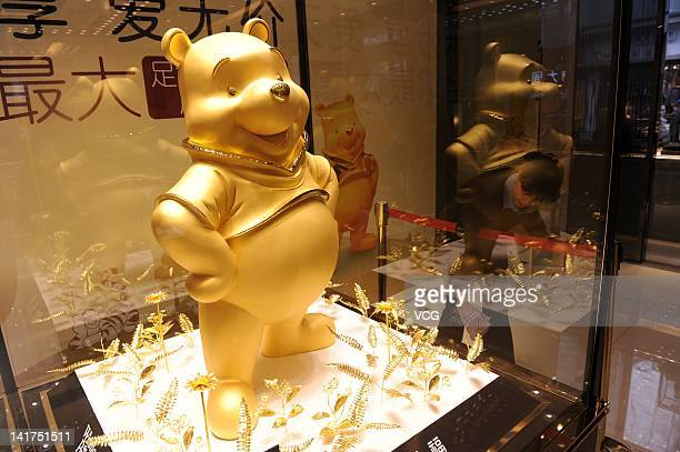 A gold figure of Winnie The Pooh is displayed inside a glass cabinet at a jewellery store on March 22 2012 in Chengdu China The 110 centimeters tall...
