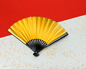 Gold folding fan on Japanese paper
