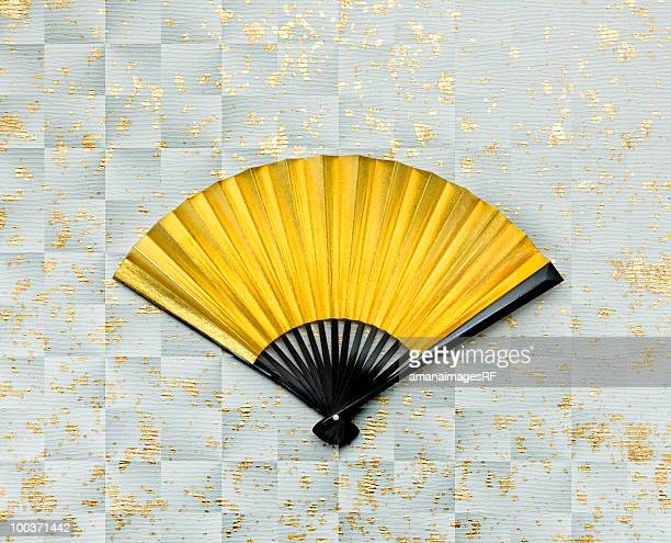 Gold folding fan on silver Japanese paper