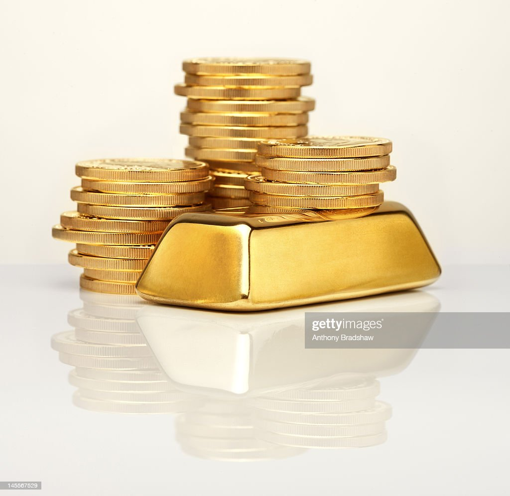 Gold ingot in front of gold coins : Stock Photo