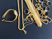 Pile of golden necklace, bracelet and rings on black background