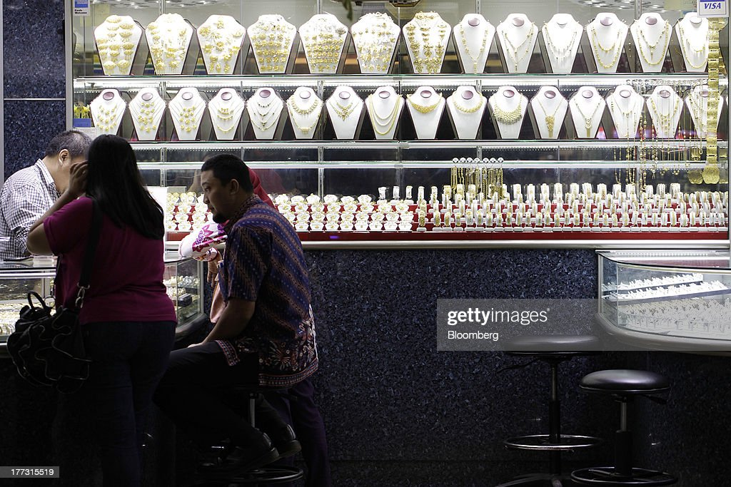 Gold jewelry sit in display cabinets as a salesperson serves customers at a jewelry store in Jakarta, Indonesia, on Thursday, Aug. 22, 2013. Gold jewelry demand in Indonesia is set to expand to a four-year high as consumers in Southeast Asia's biggest buyer join India to China in increasing purchases as prices slump and the middle class expands. Photographer: Dimas Ardian/Bloomberg via Getty Images
