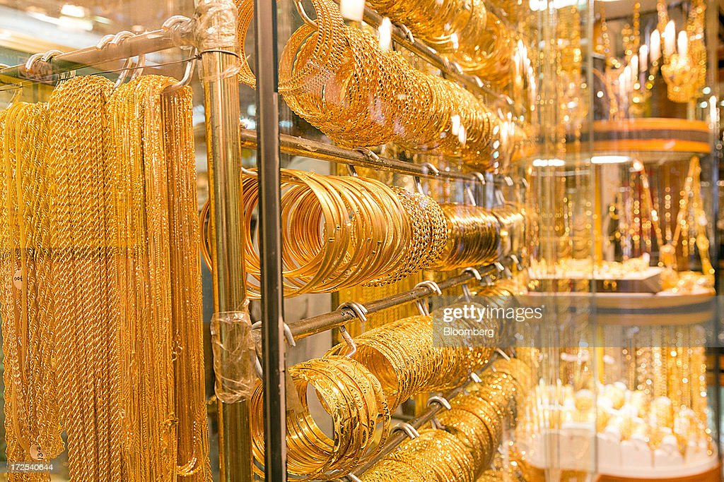 Gold jewelry sits on display in the windows of a gold store in the Dubai Gold Souk in the Deira district of Dubai, United Arab Emirates, on Tuesday, July 2, 2013. Gold swung between gains and losses in London as investors weighed prospects for increased physical demand against a slowing stimulus in the U.S. Photographer: Duncan Chard/Bloomberg via Getty Images
