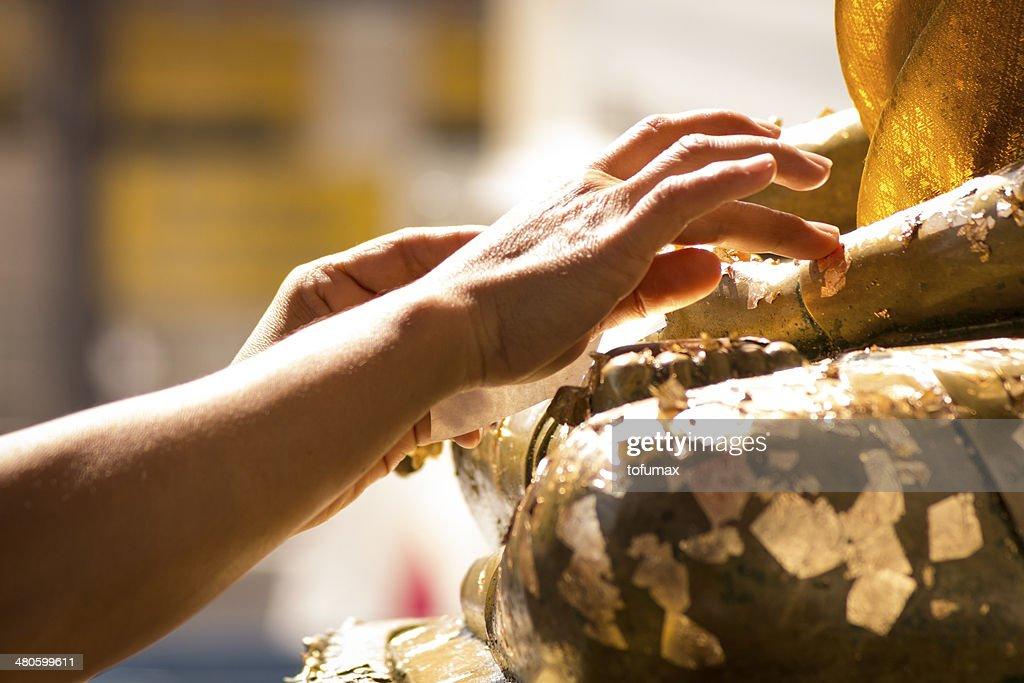gold leaf onto the Buddha image : Stock Photo