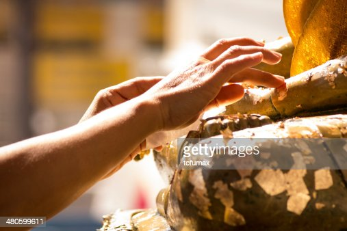gold leaf onto the Buddha image : Stock Photo