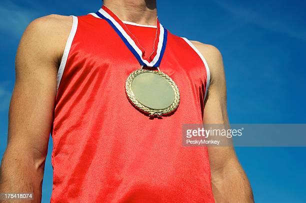 Medaglia d'oro atleta in camicia rossa in piedi in Blue Sky