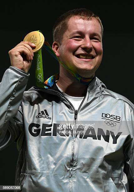 Gold medal Germany's Christian Reitz celebrates on the podium during the medal ceremony for the 25m Rapid Fire Pistol men's Finals shooting event at...