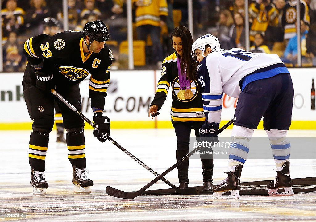 Gold medal gymnast Aly Raisman drops the puck in front of Zdeno Chara #33 of the Boston Bruins and Andrew Ladd #16 of the Winnipeg Jets during the game on January 21, 2013 at TD Garden in Boston, Massachusetts.