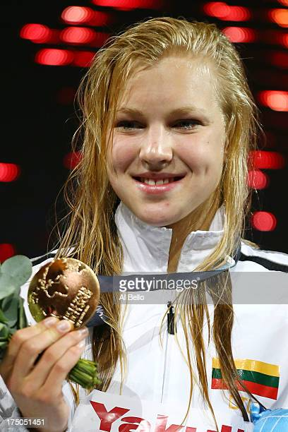 Gold medal winner Ruta Meilutyte of Lithuania celebrates on the podium after the Swimming Women's 100m Breastroke Final on day eleven of the 15th...