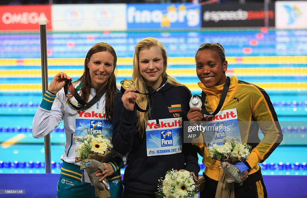 Gold medal winner Ruta Meilutyte of Lithuania (C), silver medal winner Alia Atkinson of Jamaica (R) and bronze medal winner Sarah Karsoulis of Australia pose after the women's 50m breasttroke on December 13, 2012 of the FINA World Short Course Swimming Championships in Istanbul. AFP PHOTO/MIRA