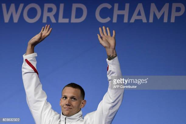 Gold medalis USA's Caeleb Remel Dressel celebrates on the podium of the men's 100m freestyle race during the swimming competition at the 2017 FINA...