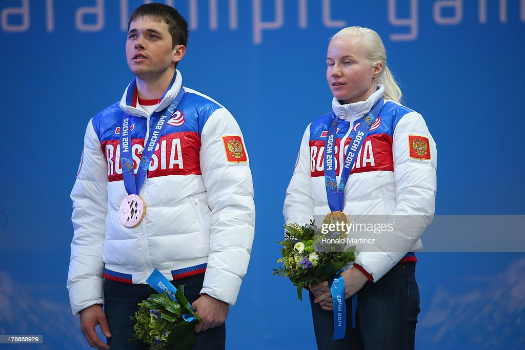 Gold medalist Aleksandra Frantceva of Russia and guide Pavel Zabotin sing the national anthem at the medal ceremony for women's Super Combined Visually Impaired on day eight of the Sochi 2014 Paralympic Winter Games at Laura Cross-country Ski & Biathlon Center on March 15, 2014 in Sochi, Russia.