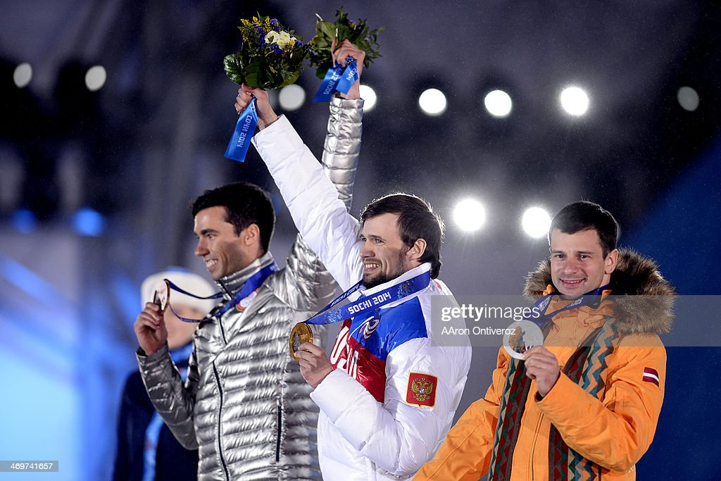 Gold medalist <a gi-track='captionPersonalityLinkClicked' href=/galleries/search?phrase=Alexander+Tretiakov&family=editorial&specificpeople=723551 ng-click='$event.stopPropagation()'>Alexander Tretiakov</a> (center) of Russia waives his flowers on the stage with silver medalist <a gi-track='captionPersonalityLinkClicked' href=/galleries/search?phrase=Martins+Dukurs&family=editorial&specificpeople=4876286 ng-click='$event.stopPropagation()'>Martins Dukurs</a> of Latvia (right) and bronze medalist Matthew Antoine of the United States (left) join the celebration during the medals ceremony for the men's skeleton. Sochi 2014 Winter Olympics on Sunday, February 16, 2014.