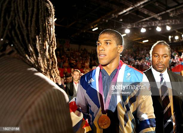Gold medalist Anthony Joshua of Great Britain shakes hands with British professional boxer and super heavyweight gold medalist Audley Harrison as...